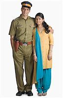 female police officer happy - Portrait of a police officer standing with his arm around his wife Stock Photo - Premium Royalty-Freenull, Code: 630-03479463