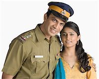 female police officer happy - Portrait of a police officer standing with his arm around his wife Stock Photo - Premium Royalty-Freenull, Code: 630-03479465