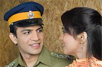 female police officer happy - Close-up of a police man with his wife looking at each other and smiling Stock Photo - Premium Royalty-Freenull, Code: 630-03479487