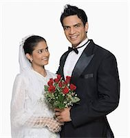 Portrait of a newlywed couple holding a bouquet of flowers and smiling Stock Photo - Premium Royalty-Freenull, Code: 630-03479491