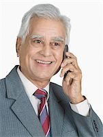 Businessman talking on a mobile phone and smiling Stock Photo - Premium Royalty-Freenull, Code: 630-03479651