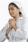 Close-up of a nun standing in the prayer position