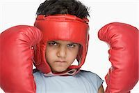 Portrait of a boy wearing boxing gloves and head protector Stock Photo - Premium Royalty-Freenull, Code: 630-03481268