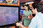 Young man playing video game and a young woman watching his game in a video arcade Stock Photo - Premium Royalty-Freenull, Code: 630-03481705
