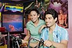 Young man playing video game and a young woman watching his game in a video arcade Stock Photo - Premium Royalty-Freenull, Code: 630-03481708