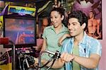 Young man playing video game and a young woman watching his game in a video arcade Stock Photo - Premium Royalty-Freenull, Code: 630-03481709