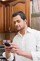 Man text messaging on a mobile phone Stock Photo - Premium Royalty-Freenull, Code: 630-03482609