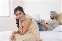 sad lovers break up - Woman looking sad while her husband working on a laptop on the bed Stock Photo - Premium Royalty-Freenull, Code: 630-03482786