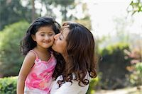 Woman kissing her daughter in a park Stock Photo - Premium Royalty-Freenull, Code: 630-03483070