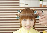 A young woman is set her hair in curlers Stock Photo - Premium Royalty-Freenull, Code: 670-03483838