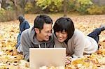Couple Using Laptop and Lying in Autumn Leaves Stock Photo - Premium Rights-Managed, Artist: Jerzyworks, Code: 700-03484885