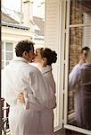 Couple kissing in front of an open window