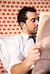 Businessman reading newspaper in bed