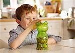 Boy putting coins into a money box in the shape of a teddy bear Stock Photo - Premium Rights-Managed, Artist: ableimages, Code: 822-03485216