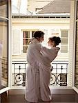 Couple hugging in front of an open window