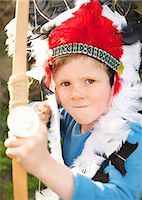 Boy wearing Indian chief feather headdress holding bow and arrow Stock Photo - Premium Rights-Managednull, Code: 822-03485234