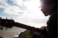 Young woman playing guitar by the ocean Stock Photo - Premium Rights-Managednull, Code: 822-03485331