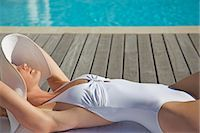 Woman in white hat and swimsuit lying by edge of swimming pool Stock Photo - Premium Rights-Managednull, Code: 822-03485348