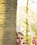 Girl hiding behind tree wearing Indian feather headdress holding bow and arrow, close up