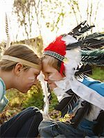 Boy and girl wearing Indian feather headdresses sitting face to face Stock Photo - Premium Rights-Managednull, Code: 822-03485497