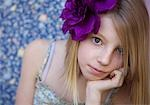 Portrait of a girl with a silk purple flower in her hair
