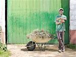Man with wheelbarrow full of hay Stock Photo - Premium Royalty-Freenull, Code: 649-03487606