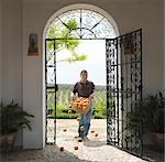 Man with basket full of oranges falling Stock Photo - Premium Royalty-Free, Artist: Robert Harding Images, Code: 649-03487637