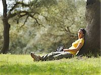 sitting under tree - Woman sleeping under a tree Stock Photo - Premium Royalty-Freenull, Code: 649-03487651