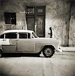 Image taken with a Holga medium format 120 film toy camera of man walking past old American car, Havana, Cuba, West Indies, Central America