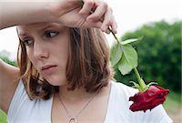 sad lovers break up - Teenage Girl Holding a Red Rose Stock Photo - Premium Royalty-Freenull, Code: 600-03490326