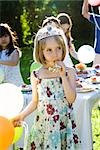 Girl wearing tiara and blowing party horn blower at outdoor party Stock Photo - Premium Royalty-Freenull, Code: 632-03500973