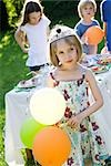 Girl wearing tiara and holding balloons at outdoor party Stock Photo - Premium Royalty-Freenull, Code: 632-03500998