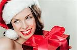 Young brunette woman wearing Santa hat with Christmas present