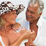 Senior couple on beach, man applying suncream to woman Stock Photo - Premium Rights-Managed, Artist: Robert Harding Images, Code: 841-03507719
