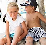 Boy and girl (6-8) on beach by windsurfer