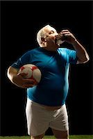 fat man balls - Large footballer holding ball and eating Stock Photo - Premium Royalty-Freenull, Code: 649-03511269
