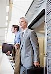 Businessmen exiting train in train station Stock Photo - Premium Royalty-Freenull, Code: 635-03515544