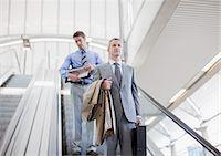 Businessmen descending escalator Stock Photo - Premium Royalty-Freenull, Code: 635-03515581