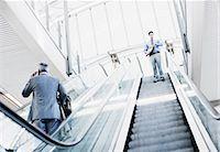 Businessman descending escalator Stock Photo - Premium Royalty-Freenull, Code: 635-03515584