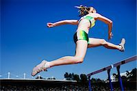 Runner jumping hurdles on track Stock Photo - Premium Royalty-Freenull, Code: 635-03515691