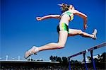 Runner jumping hurdles on track Stock Photo - Premium Royalty-Freenull, Code: 635-03515691