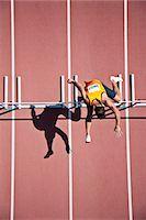 Runner jumping hurdles on track Stock Photo - Premium Royalty-Freenull, Code: 635-03515700