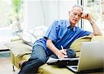 Businessman using laptop on sofa Stock Photo - Premium Royalty-Freenull, Code: 635-03515893