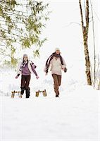 Mother and daughter pulling sleds through snow Stock Photo - Premium Royalty-Freenull, Code: 635-03516137