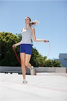 Woman skipping rope in urban plaza Stock Photo - Premium Royalty-Freenull, Code: 635-03516190