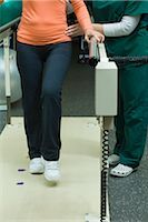 rehabilitation - Patient learning to walk and regain leg coordination with assistance from physical therapist Stock Photo - Premium Royalty-Freenull, Code: 632-03516799