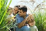 Family crouching together in tall grass