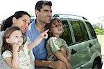 Family leaning against car, all looking as daughter points at something in distance