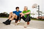 Father and Son Sitting on Basketballs on Court Stock Photo - Premium Rights-Managed, Artist: Peter Griffith, Code: 700-03519160