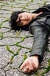 young man laying on cracked pavement Stock Photo - Premium Rights-Managed, Artist: Asia Images, Code: 849-03519401